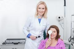 Skillful ophthalmologist is examining human vision in office - stock photo
