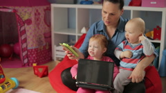 Mother spend time with kids and showing something on smartphone - stock footage