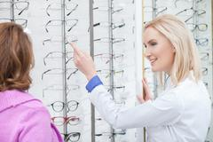 Cheerful female optometrist is consulting mature lady - stock photo