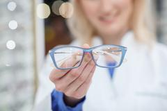 Cheerful young oculist is showing new glasses Stock Photos