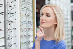 Attractive young lady is buying new spectacles - stock photo