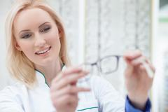 Pretty female ophthalmologist is showing new glasses - stock photo