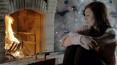 Beautiful pensive young woman kneeled in front of a fireplace Stock Footage