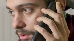 young man listens to his girlfriend complaining at the phone, portrait - stock footage