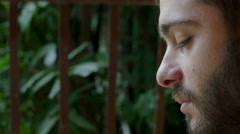Profile view of a guy sat at in his home garden, mouth closed suddenly shouts Stock Footage