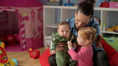 Mother teachs little baby how take care of her brother  - stock footage