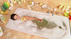 Woman taking  foam bath  and  chiropody by wisp of bast in her bathroom Stock Footage