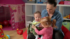 Mother teachs daughter how take care of her brother   - stock footage