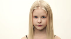Girl with blond hair shows various emotions on a light background. sad mood Stock Footage