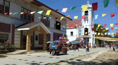 Tricycle passing by in front of the Santo Nino de Anda Parish Church Stock Footage