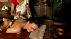 Woman having ayurvedic back massage with pouch of rice. One can see only hands - stock footage