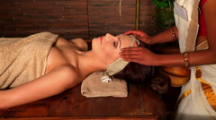 Woman having oil Ayurveda spa treatment. Hands professional masseuse doing Stock Footage