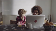 Mother with son teaching on laptop in kitchen Stock Footage