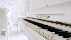 Old white piano keyboard closeup video shooting. Cozy white interior Stock Footage