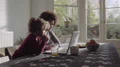 Mother with son teaching on laptop in kitchen - stock footage