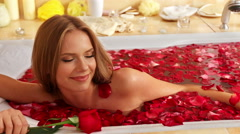 Girl taking bath with rose petals in bath Stock Footage