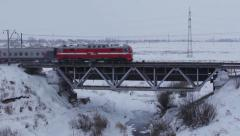 Passenger Train passes over bridge in winter Stock Footage