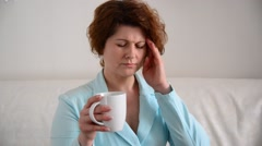 Middle-aged woman with a headache takes tablet Stock Footage