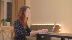 Young woman working at a laptop at home Stock Footage
