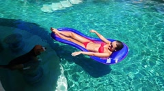 Girl with a beautiful body is relaxing on an air mattress in a pool. Dog Stock Footage