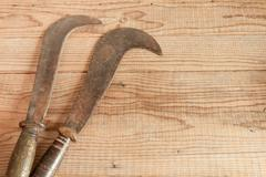 Two dated and used billhooks on wooden background - stock photo