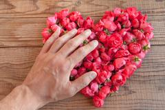 Heart made of red roses in wooden background, covered by an hand to represent - stock photo