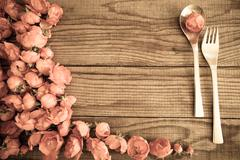 Spoon and fork over a wooden table with red roses, vintage effect - stock photo