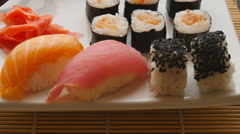 Various sushi on white plate on wooden background Stock Footage