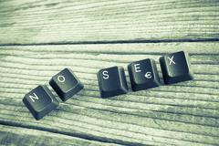 """""""NO SEX"""" wrote with keyboard keys on wooden background, green vintage effect - stock photo"""