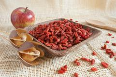 Goji beans in a wooden cup Stock Photos