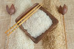 Uncooked Minerbe, Ribe and Basmati rice in a wooden cup - stock photo