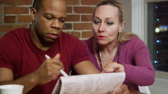 Man and Woman doing a Crossword Puzzle together in newspaper Stock Footage
