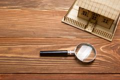 Real Estate Concept. Model house and magnifying glass on wooden table. Top view - stock photo