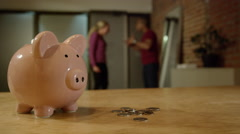 Married couple fighting about money - Piggy bank in foreground Stock Footage