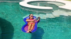 Girl with a beautiful body is relaxing on an air mattress in a pool. Female Stock Footage