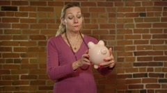 Middle aged woman is worried about her finances - piggy bank savings Stock Footage