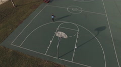 Boy practicing shots on basketball court aerial shot 4k Stock Footage