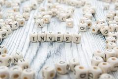 Invest word written on wood block. wooden abc Stock Photos