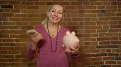 Grandmother holding piggy bank and money - Retirement planning Stock Footage