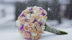 Colorful bridal beautiful bouquet of different flowers in snowfall Stock Footage