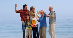 Multi generation family jumping on the beach - stock footage