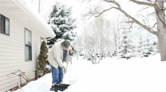 Aging man shovels snow pauses to stretch his aching back and wipe Stock Footage