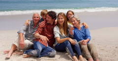 Multi generation family sitting on the beach - stock footage