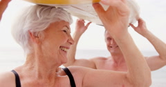 Retired couple holding surfboard over their heads Stock Footage