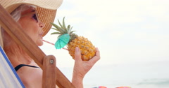 Retired woman drinking cocktail and lying on deckchair Stock Footage