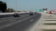 A Man walking beside Al Fatih Highway, Manama, Bahrain. He stumbles. Stock Footage