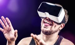Man uses Virtual Reality VR head-mounted display with fun - stock photo