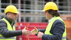 Engineers with safety jackets and hardhats reaching agreement Stock Footage