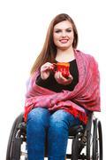 Woman invalid girl on wheelchair holds tea mug - stock photo