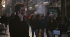Blonde man talking on cell phone in shopping street Stock Footage